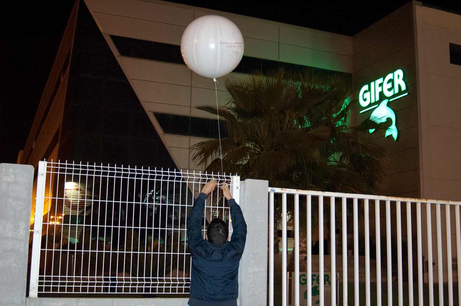Instalación nocturna de globos de Helio gigantes en acceso a empresas